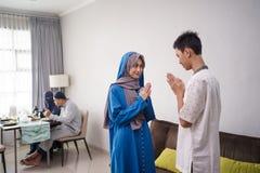 Asian muslim family sibling shake hand in idul fitri eid mubarak