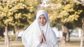 Asian muslim girl Do Thai Greeting. An attractive Thai girl demonstrate the typical Thai wai greeting outdoor at university park Stock Photography