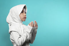 Asian muslim girl in hijab raising hand and praying Stock Image