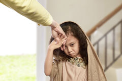 Asian muslim girl kissing hand parents as respect. In the home stock image