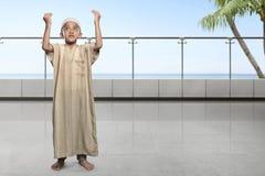 Asian muslim kid with cap raising hand and praying Stock Images