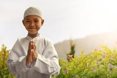 Asian muslim kid. Greeting at garden Royalty Free Stock Photo