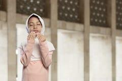 Asian muslim kid in hijab praying to god Stock Photos
