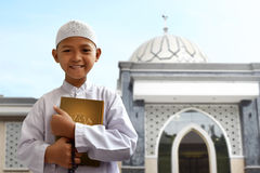 Asian muslim kid. Holding koran royalty free stock image