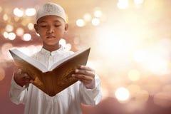 Asian muslim kid reading koran. With bokeh background Royalty Free Stock Photo