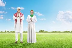 Asian muslim man with cap and muslim woman with veil praying together on the green grass field stock images