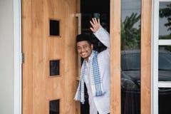 Muslim man greeting. Asian muslim man at his front door greeting guest Stock Photo
