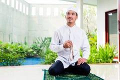 Asian Muslim man praying at home Stock Image