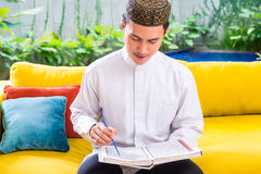 Asian Muslim man reading Koran Royalty Free Stock Photography