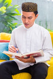 Asian Muslim man reading Koran Royalty Free Stock Image