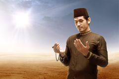 Asian muslim man standing and praying while raised arms with prayer beads on desert. With sun rays and dark sky background stock image
