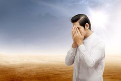 Asian muslim man standing and praying while rubbing the face in desert royalty free stock photo