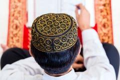Asian Muslim man studying Koran or Quran. Asian Muslim men reading Koran or Quran on praying carpet wearing traditional dress Stock Photography