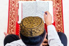 Asian Muslim man studying Koran or Quran Stock Photo