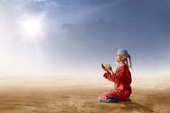 Asian muslim man with turban in his head kneeling and praying with raised hands on desert. With sun rays and dark sky background royalty free stock images