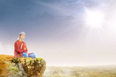 Asian muslim man with turban in his head sitting and holding the quran on the edge of the cliff stock photography