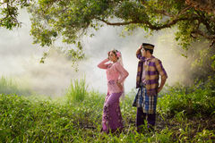 Asian Muslim man and woman wearing traditional dress. Asian Muslim men and women wearing traditional dress in dancing action Stock Photo