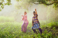 Asian Muslim man and woman wearing traditional dress. Asian Muslim men and women wearing traditional dress in dancing action Stock Images