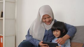 Asian muslim mom and little baby girl daughter learning online or watching videos on tablet phone, happiness between mother and