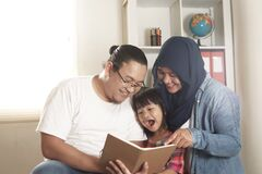 Free Asian Muslim Parent, Mother, Father And Child Are Reading A Book At Home, Happy Excited Expression Royalty Free Stock Photo - 188047385