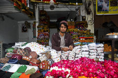 Asian Muslim Shopkeeper. An Asian Muslim shopkeeper selling caps, flowers and sweats at Data-Darbar Lahore, Pakistan Royalty Free Stock Photography
