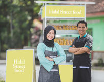 Asian muslim small food stall owner. Young asian muslim small food stall owner, standing proudly with her partner at the background. halal street food concept Stock Photos
