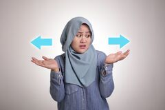 Free Asian Muslim Woman Confused To Decide A Choice. Choose Left Or Right Direction Arrow Concept Royalty Free Stock Photography - 190879457
