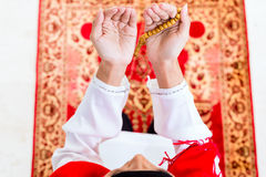 Asian Muslim woman praying with beads chain. Asian Muslim woman praying on carpet with beads chain wearing traditional dress Royalty Free Stock Images