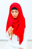 Asian Muslim woman praying with beads chain. Wearing traditional dress Royalty Free Stock Photography