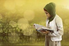 Asian muslim woman reading koran Royalty Free Stock Image