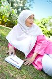 Asian Muslim woman reading outdoor. Stock Photography