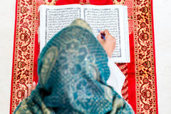 Asian Muslim woman studying Koran or Quran Stock Photography