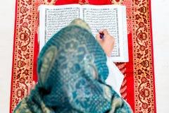 Asian Muslim woman studying Koran or Quran Stock Photography