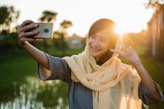 Asian muslim woman take selfie with mobile phone. Outdoor during sunset stock photography
