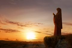 Asian muslim woman in veil raised hands and praying on the edge of the cliff. With sunset and landscapes background royalty free stock photo