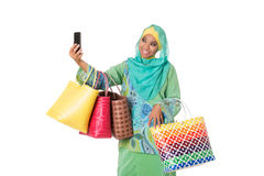 Asian muslimah woman with bright wicker tote bags taking selfie. Stock Photo