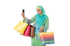 Asian muslimah woman with bright wicker tote bags taking selfie.Isolated Stock Photography