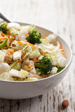 Asian Napa cabbage salad on weathered white wood. Side view of an Asian Napa cabbage salad with organic broccoli, almonds, chicken, and a rice vinaigrette on Stock Images