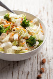 Asian Napa cabbage salad on wood. Asian Napa cabbage salad with organic broccoli, almonds, chicken, and a rice vinaigrette on weathered white wood Royalty Free Stock Photography