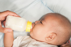 Asian newborn baby drinking milk from bottle. Royalty Free Stock Photography