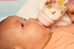 Asian newborn baby drinking milk from bottle. Royalty Free Stock Images