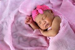 Asian newborn baby sleepin in pink cloth wearing headband royalty free stock photo