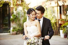 Asian newly wed couple riding a bicycle. Happy newly wed asian couple having fun riding a bicycle Royalty Free Stock Photos