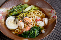 Asian noodle soup with crap meat, boiled egg, shrimp, spinach. Closeup with selective focus.  Stock Image