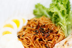 Asian noodles. Close up of Asian dry noodles surrounded by condiments and garnishing Stock Image