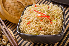 Asian Noodles. Asian style noodles with bamboo steamer, dried mushrooms, and chopsticks royalty free stock photos