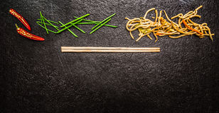 Asian noodles with chopstick, red chili ,chopped chives on black slate background, top view, banner Royalty Free Stock Images