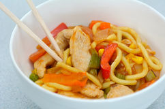 Asian noodles dish. Of chicken and vegetables served in a bawl and chopsticks stock photos