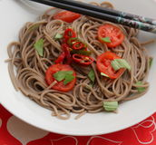 Asian noodles. Some asian somen noodles with tomatoes and chili royalty free stock photo