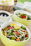 Asian noodles on table. Asian noodles on bamboo mat with focus pointed in front of dish and shallow DOF Royalty Free Stock Image